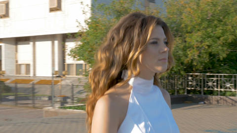 A beautiful woman in white clothes is walking along the street Image