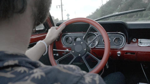 Hipster Drives Vintage Car with Orange Steering Wheel Footage
