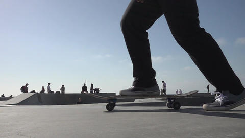 Closeup of legs skateboarding at a west coast skate park Footage
