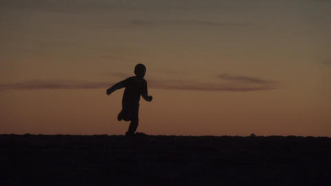 Child Running at Sunset Silhouette Footage