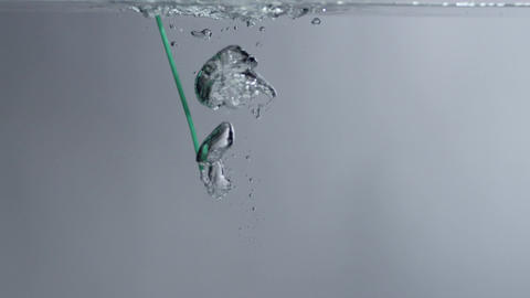 Bubbles shoot out of a green straw in clear liquid w/ white BG Footage