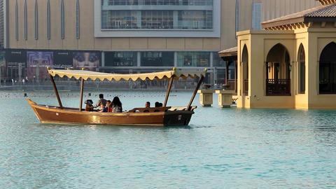 Water taxi, pleasure boat at Burj Khalifa lake. Telephoto view, vessel sail away Footage
