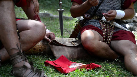 Roman soldiers sitting on a trunk felled in the forest and eat out of a piece of Footage