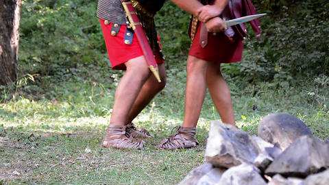 Roman soldiers struggling in the forest, one of them falls pierced by the sword  Footage