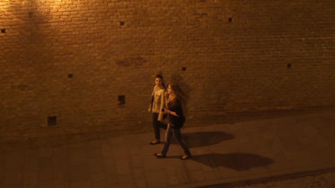Girls walking on an alley bordered by a high wall of brick and lit by lanterns y Footage