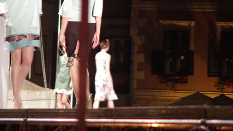 Mannequins parade on stage suspended in front of people come to watch and admire Footage