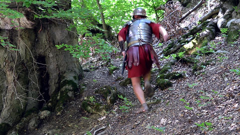 Roman soldier on a slope uphill run to hide in the woods and escape pursuers 69 Footage