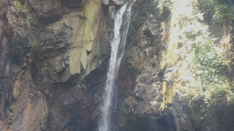 Crystal clear mountain waterfall with sun flares stock video footage Footage