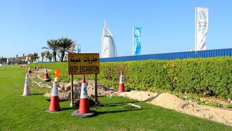 Deep excavation sign and warning cones around ditch along grass lawn Footage