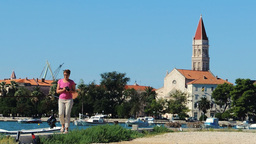 Woman taking photos and walking towards the camera Trogir Old Town background Footage