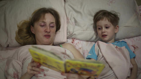 Mom reading the book to son bedtime Footage