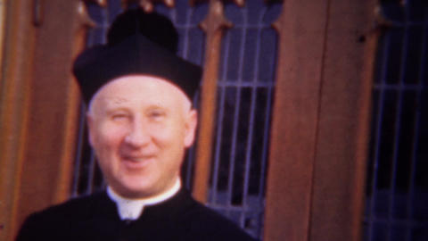 1948: Catholic deacon priest smiles in front of church windows Footage
