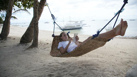 Girl in the hammock with the tablet on the beach Footage