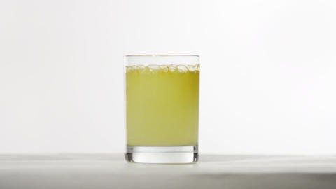 A glass of yellow liquid bubbles in front of a white background Footage