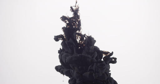 A cloud of black ink from top of frame plumes in clear liquid. Isolated Footage