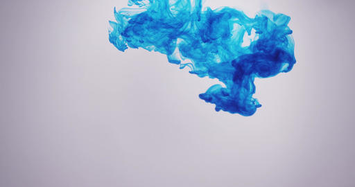 A cloud of blue ink from top of frame plumes in clear liquid. Isolated Footage