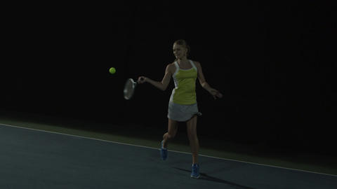 Woman plays tennis on dark court at night, returning serve, slow motion Footage