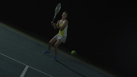 Woman plays tennis on court at night, wide shot in slow motion Footage