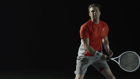 A male tennis player returns a serve and then hits the ball once more Footage