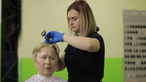 Senior woman dying hair at the beauty salon Live Action