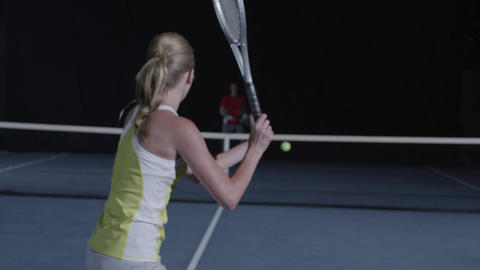 Over the shoulder shot of a woman playing tennis in slow motion Footage