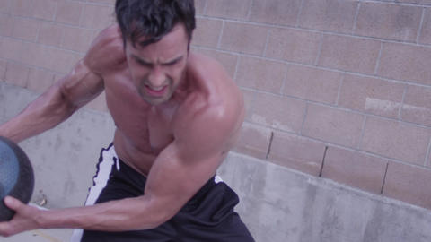 A strong man doing medicine ball exercises in slow motion Footage