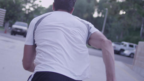 Following a male runner from behind in slow motion - fitness Footage