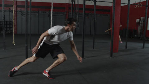 Tracking shot following a man sprinting in a gym with a woman in the background Footage