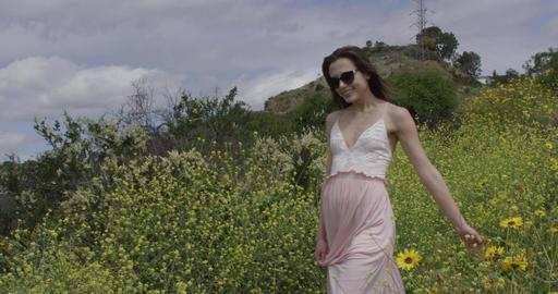 Woman Walks Through Yellow Flowers Footage