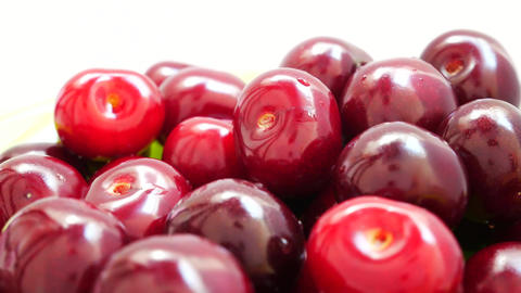 Group of Ripe Juicy Red Dark Cherry Rotates on the White Background Footage