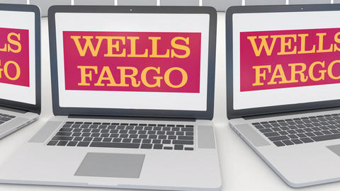 Laptops with Wells Fargo logo on the screen. Computer technology conceptual Footage