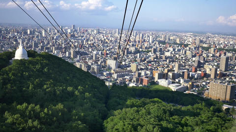 wide shot of sapporro city from a cable car going up mountain moiwa, hokkaido, Image