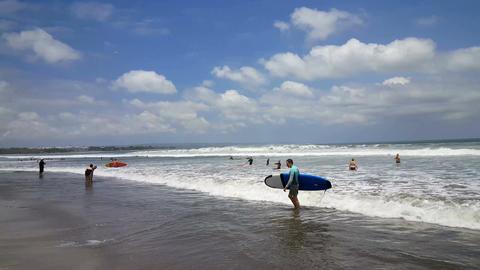 Wave surfers at the sea of Kuta beach, Bali, panshot Footage
