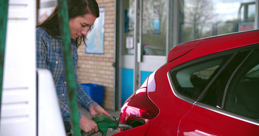 Woman refuelling a car at a petrol station Footage