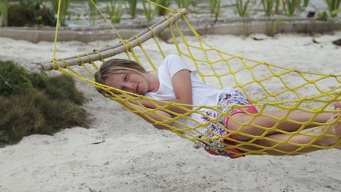 Young girl relaxing in a hammock on the sea beach Footage
