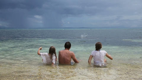Father with daughters throw pebbles into the sea Footage
