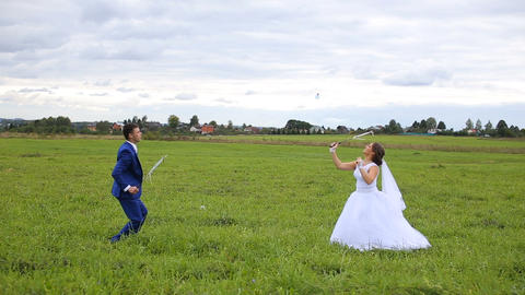 Newlyweds playing badminton on green meadow Footage