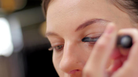 Makeup artist making up model with mascara close up Footage