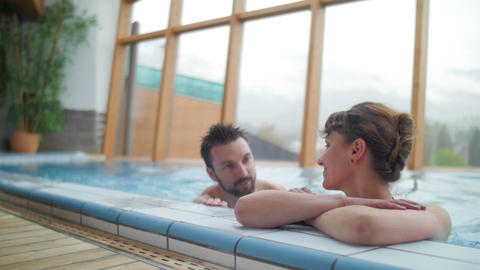 Young couple relaxing in the swimming pool wide Footage