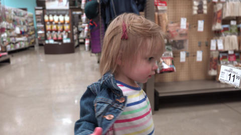 Toddler inspecting prices at pet store in cute jean jacket clothes Footage