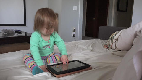 Toddler tablet computing in living room seated on white day bed Footage