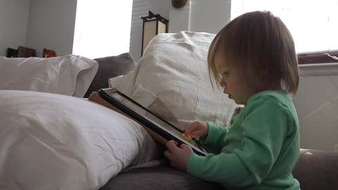 Toddler tablet computing closeup with bright window light background Footage