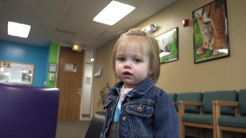 Toddler in jean jacket reaching at pediatrics doctors office waiting room Footage