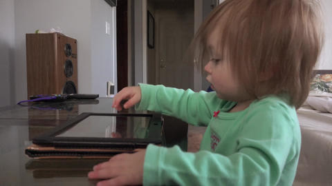 Toddler tablet computer taps and swipes closeup on coffee table Footage