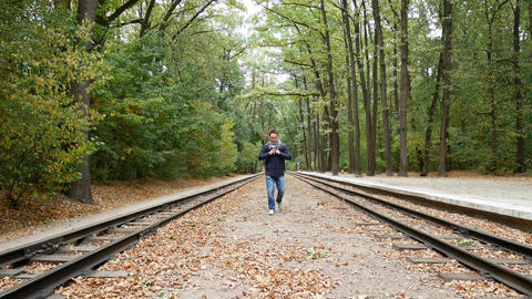 Man walks along platform between the railway rails Footage
