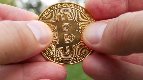 Crypto currency BTC Bitcoin coins in hands Footage