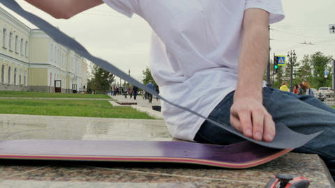 Guy puts a rough surface on the skateboard Footage