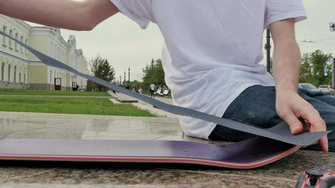 Guy aligns the rough surface and puts it on the skateboard Footage