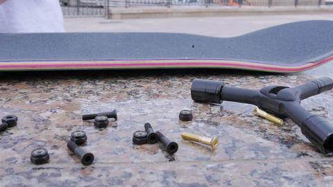 Young guy screws the bolts into a skateboard lying on the ledge Footage