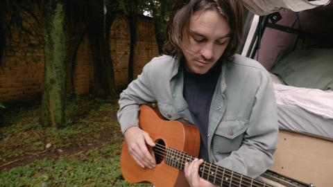 Singer songwriter musician writing a song while on the road camping in his Footage